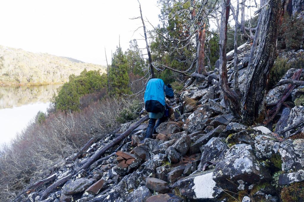 walking-over-rocks-next-to-lake-ball-tasmania