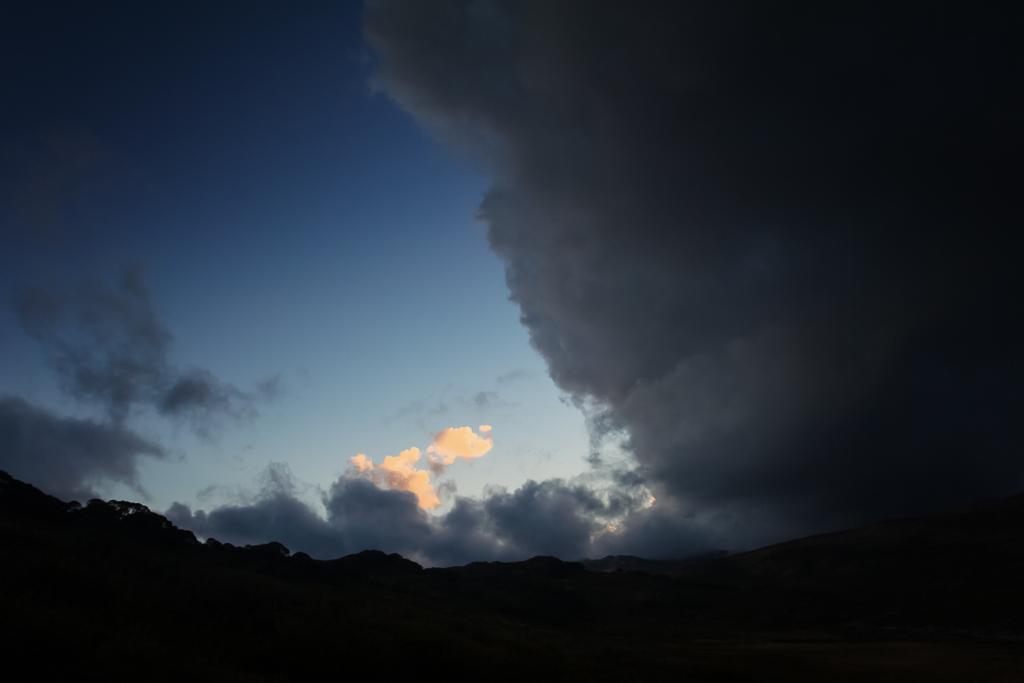 dark-clouds-sunset-snowy-mountains