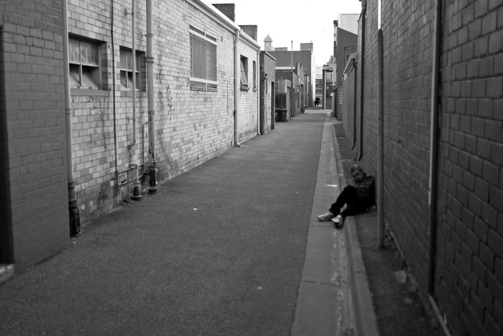 man-lying-laneway-melbourne