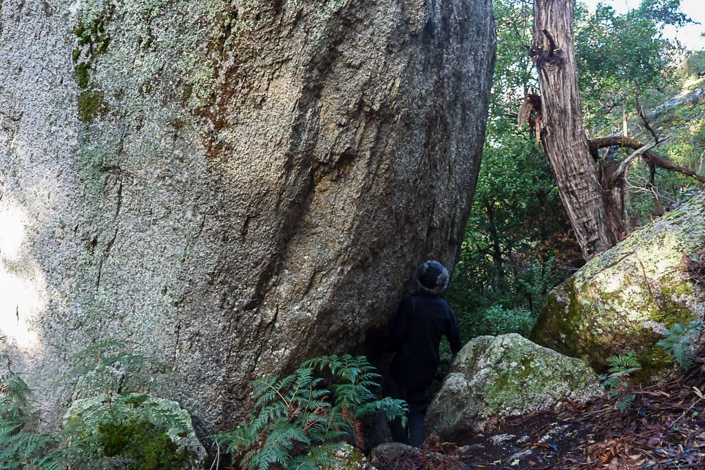 squeezing-past-large-boulder-south-point-track