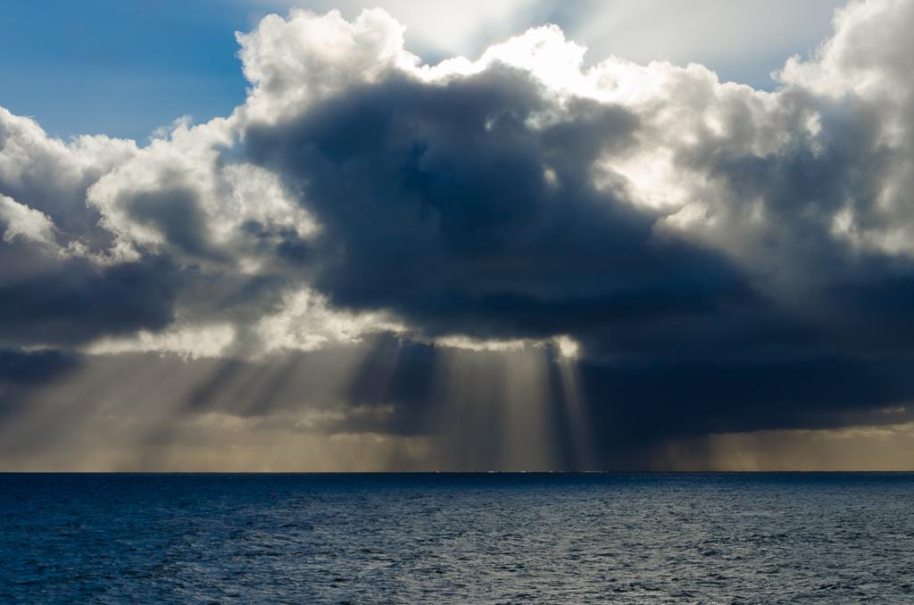 sun-ray-through-clouds-over-ocean