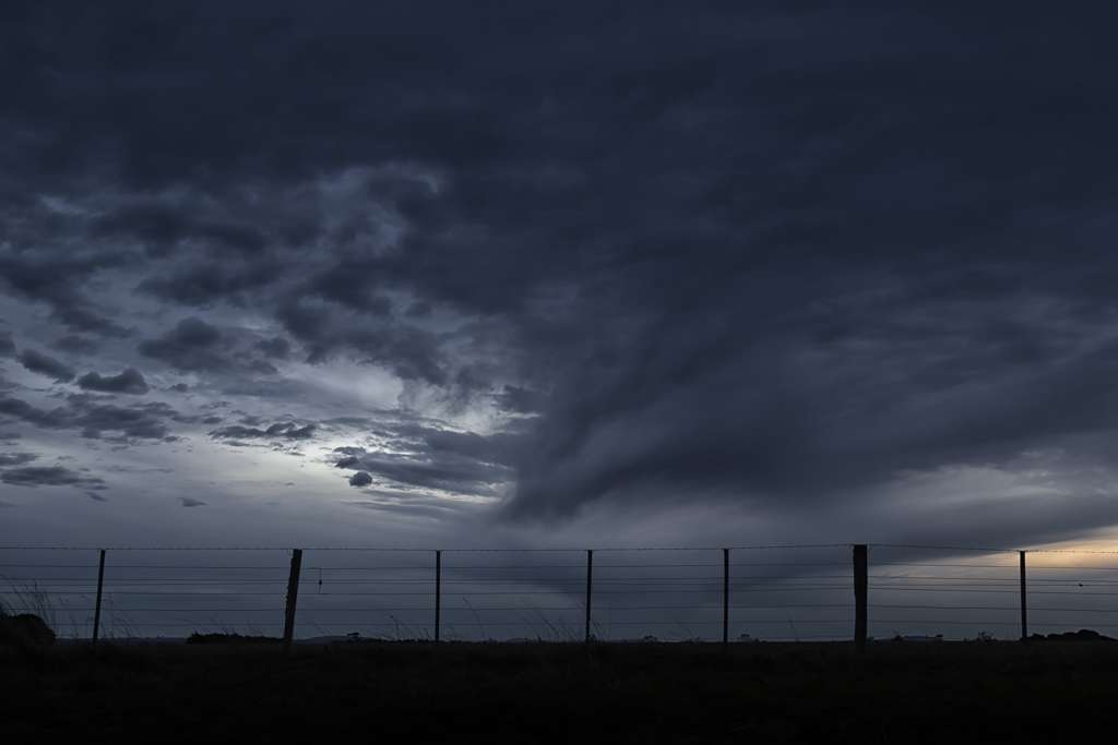 dark-clouds-over-barbed-wire-fence