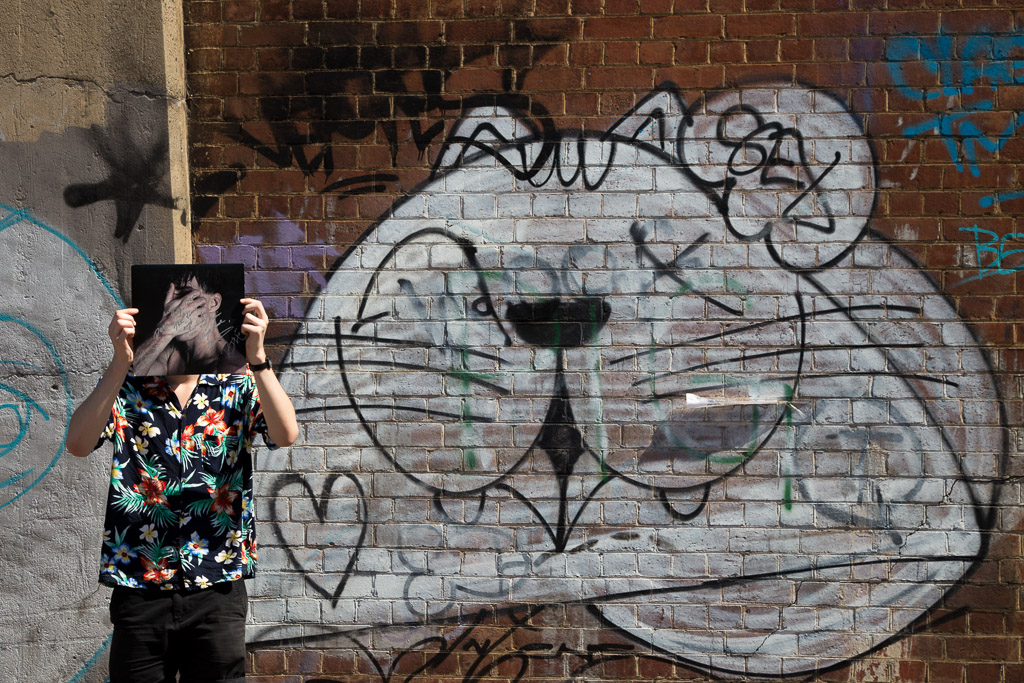 holding-record-in-front-graffiti-cat