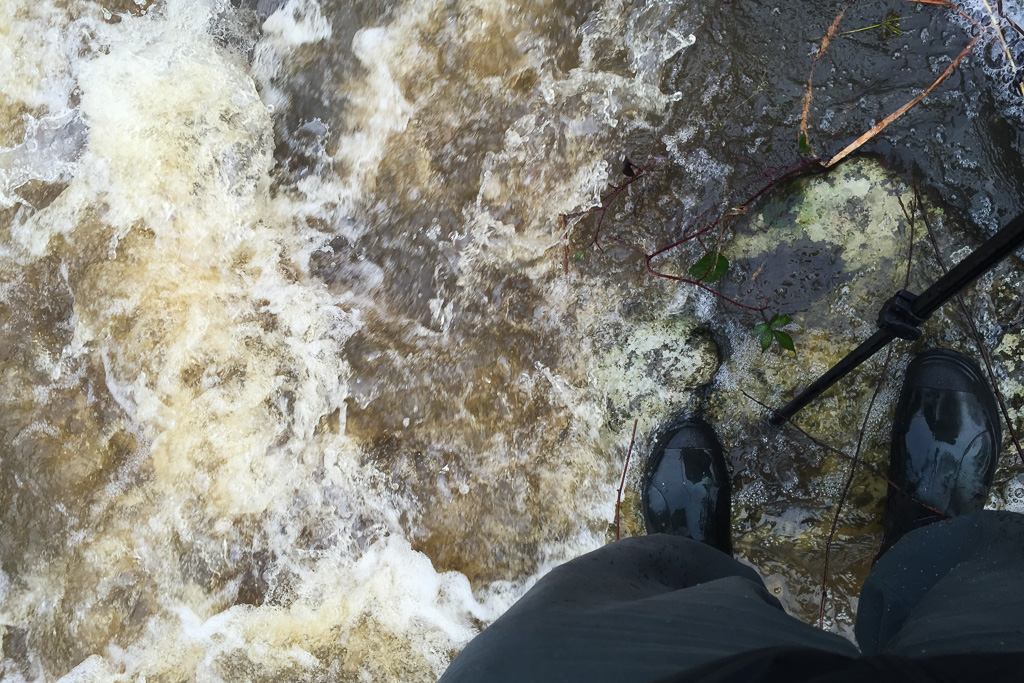 standing-on-rock-gumboots-water